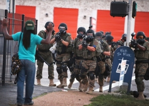 "Microcosm: an unarmed protester in Ferguson, Missouri confronts a heavily armed police force in the wake of Michael Brown's shooting. ""Hands up. Don't shoot."" (Scott Olson: Getty)"